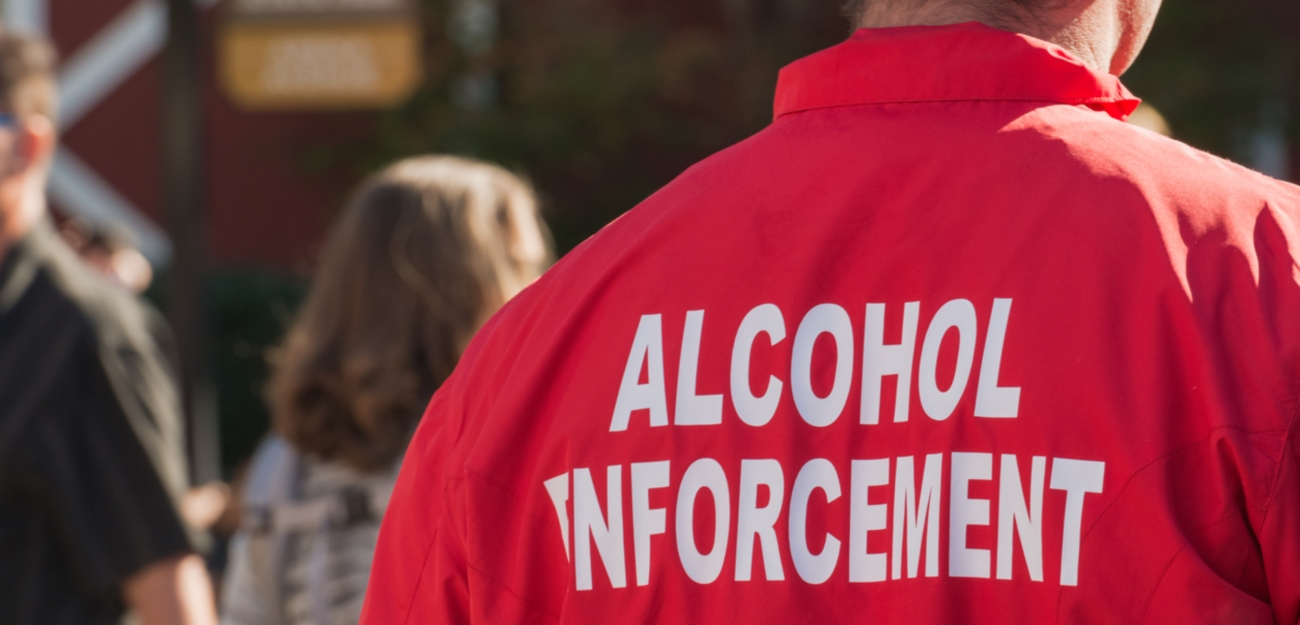 An unrecognizable person wearing a Alcohol Enforcement jacket.